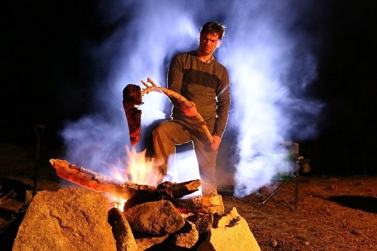 Man Holding Steak Over Fire