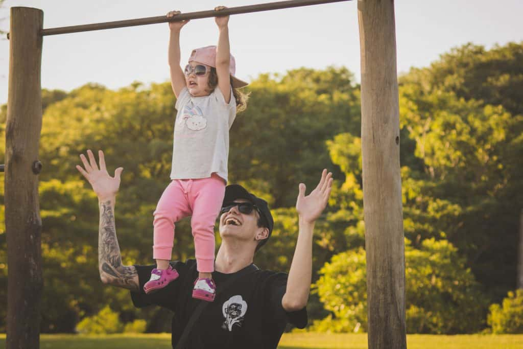 Hipster Dad playing with daughter on swing