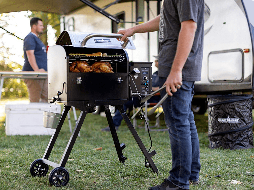 Camp Chef Pursuit 20 Portable Pellet Grill Smoker cooking chicken outside trailer