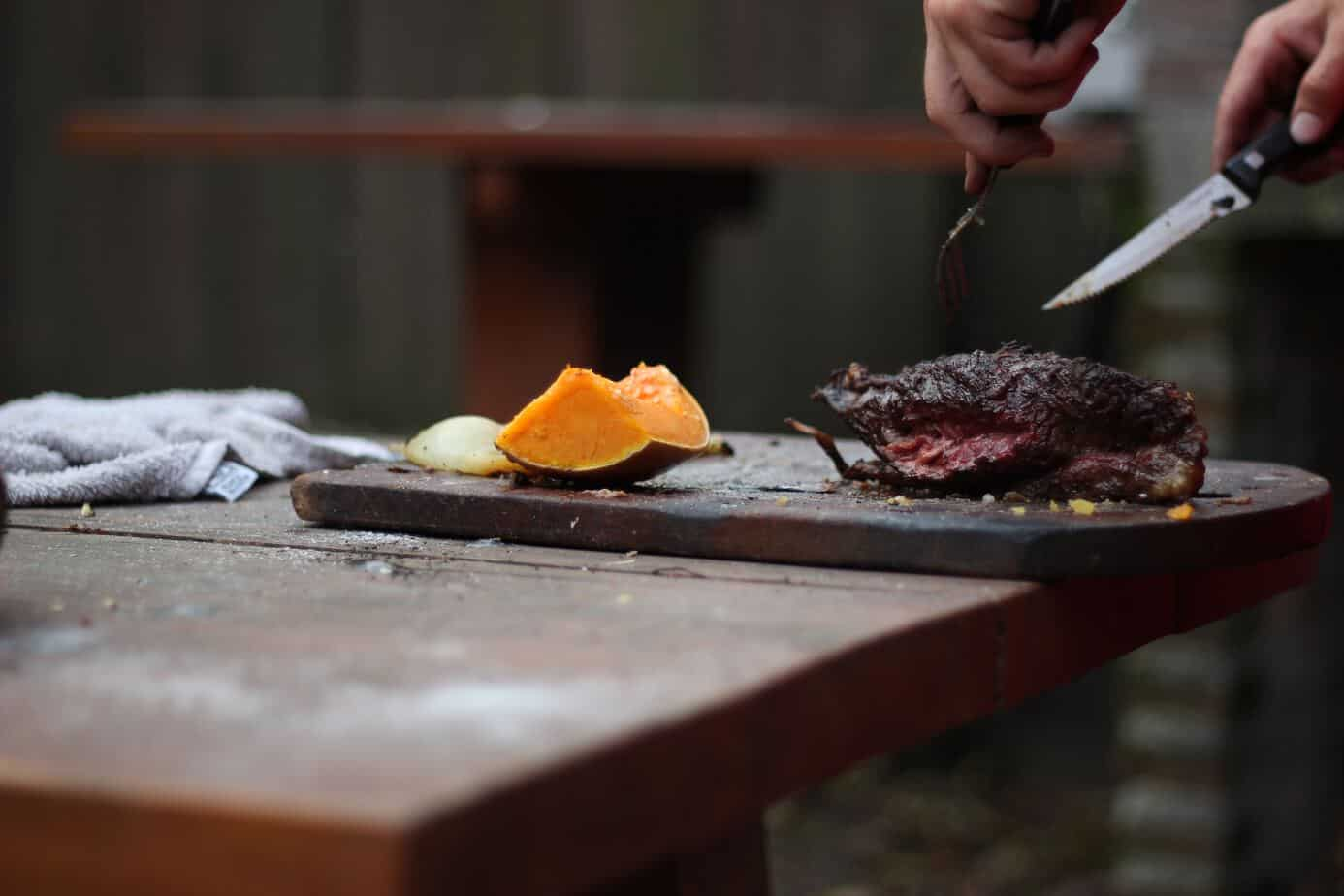 slicing smoked brisket on a cutting board