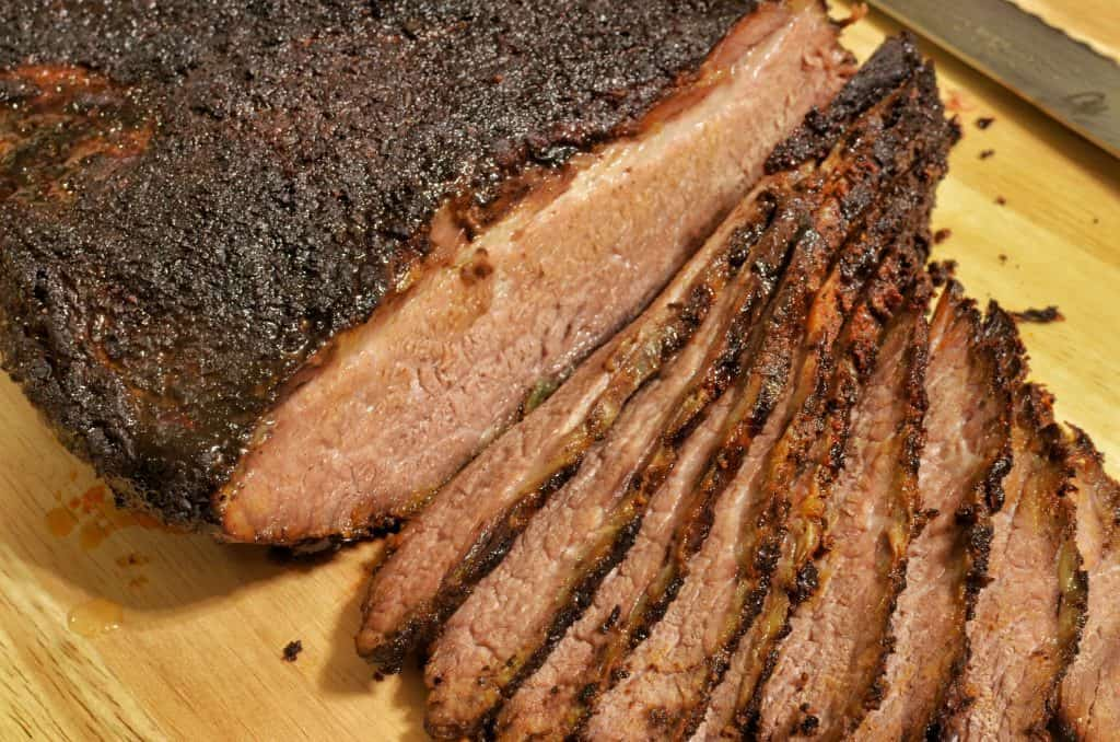 texas styled smoked brisket sliced and served on wooden cutting board