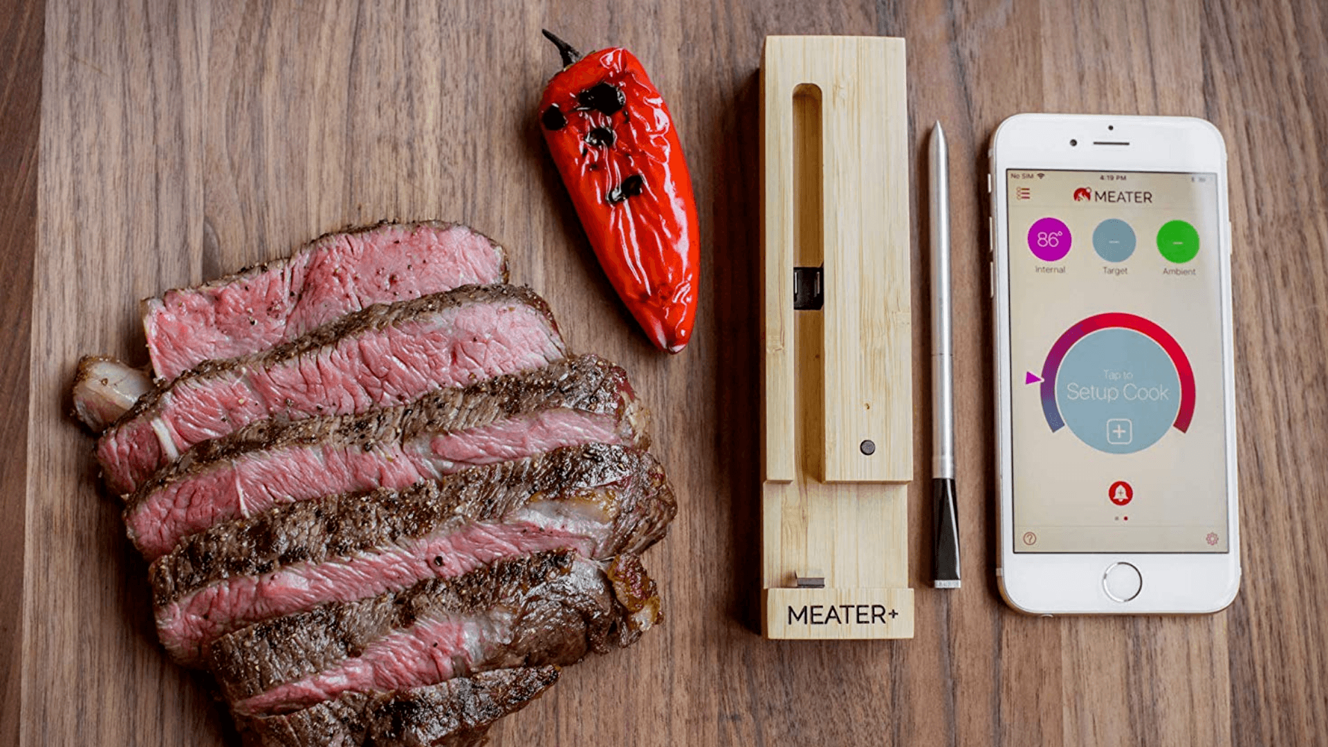 Piece of meat and grilled pepper beside meater meat thermometer and phone app