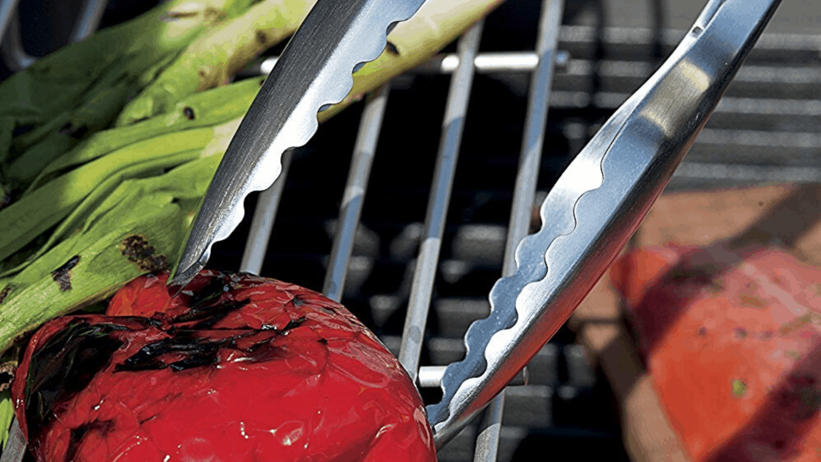 image of weber 6610 tongs being used to pick up grilled veggies