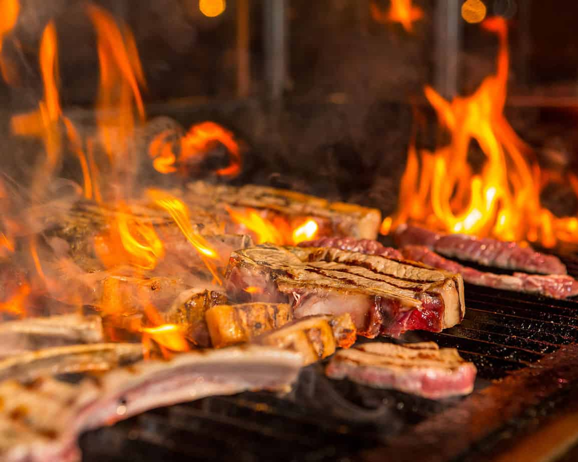 Meat steaks in flames on the grill
