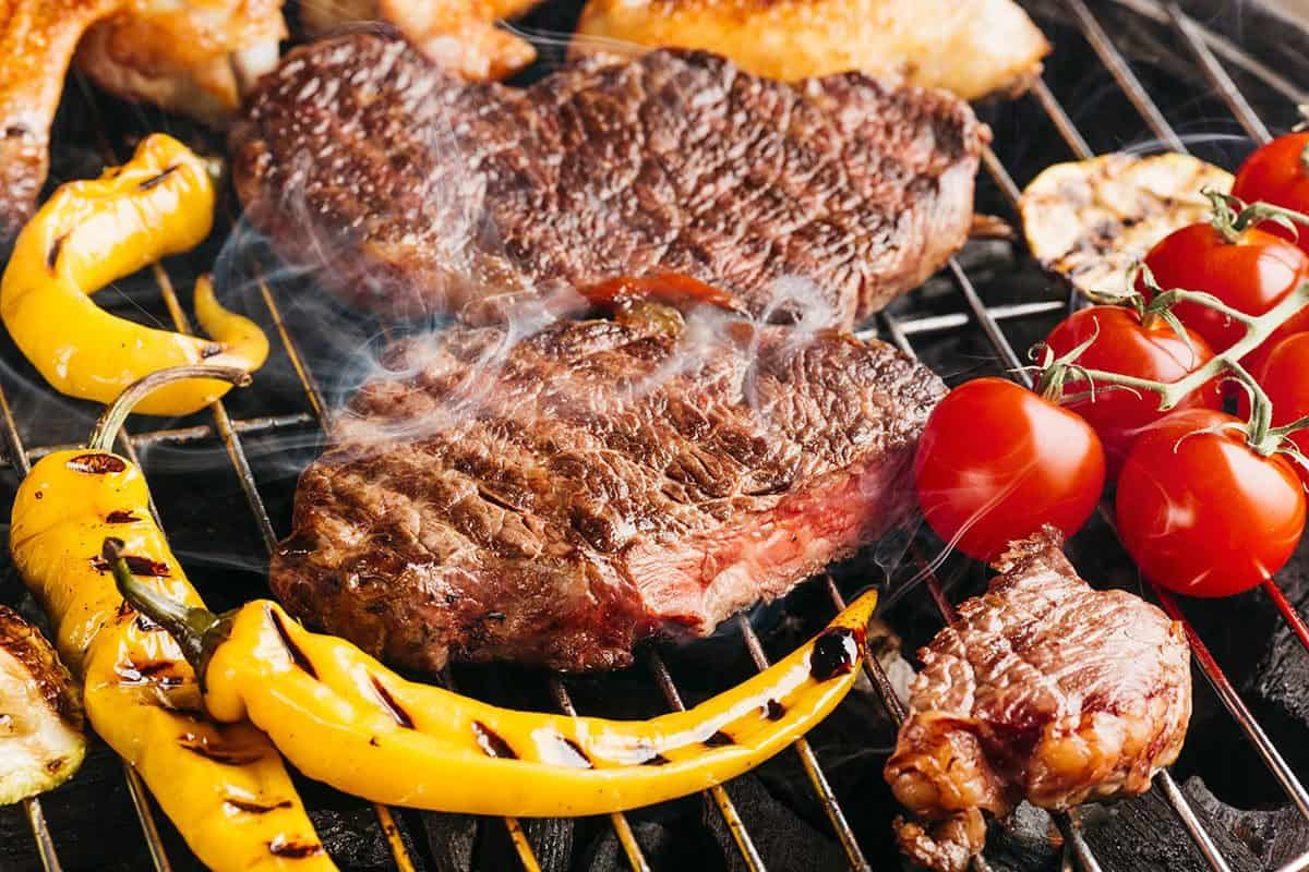 Beef steaks on grill with chili and cherry tomatoes
