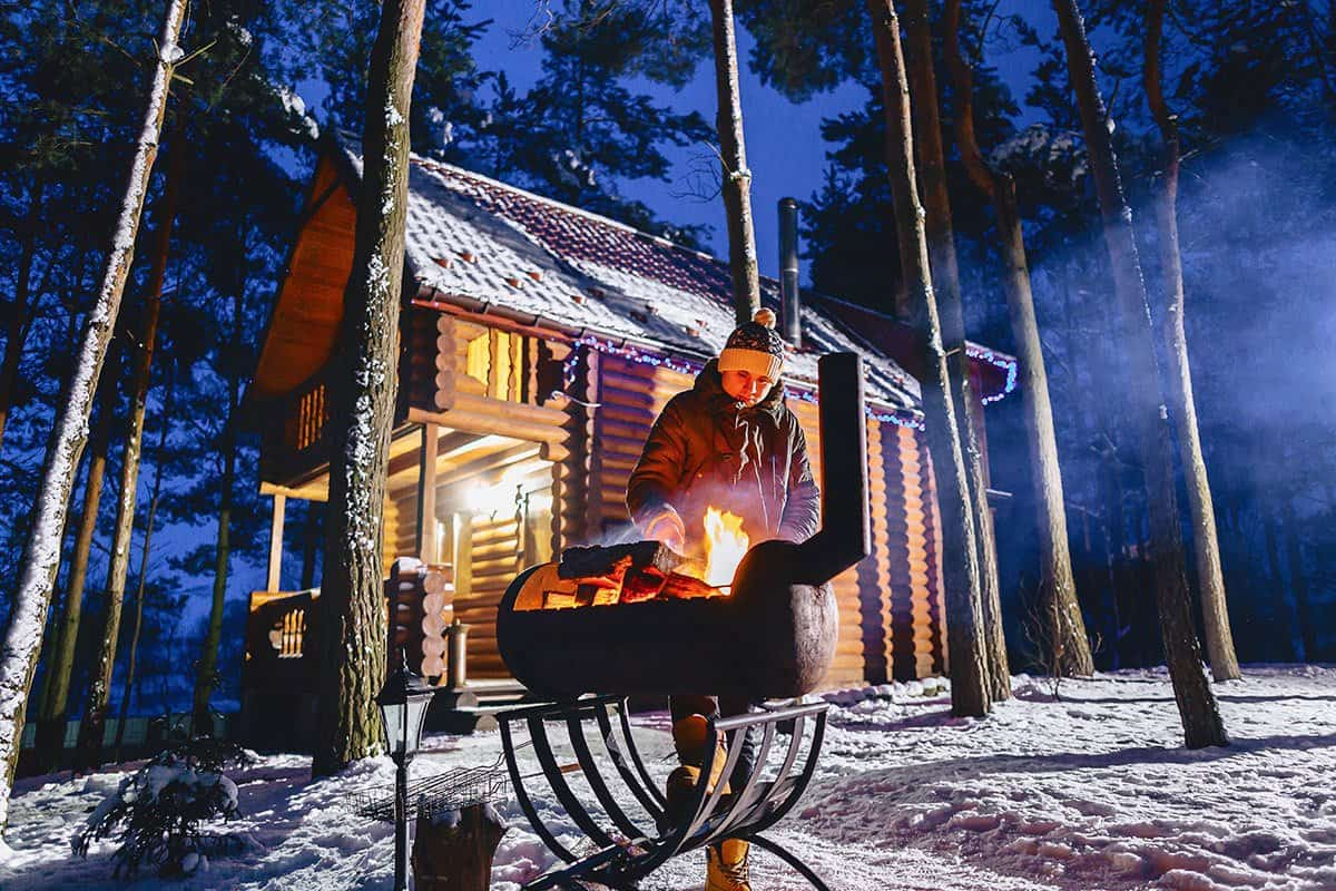 A man fries grilled meat against the cottage in the evening and in the snow