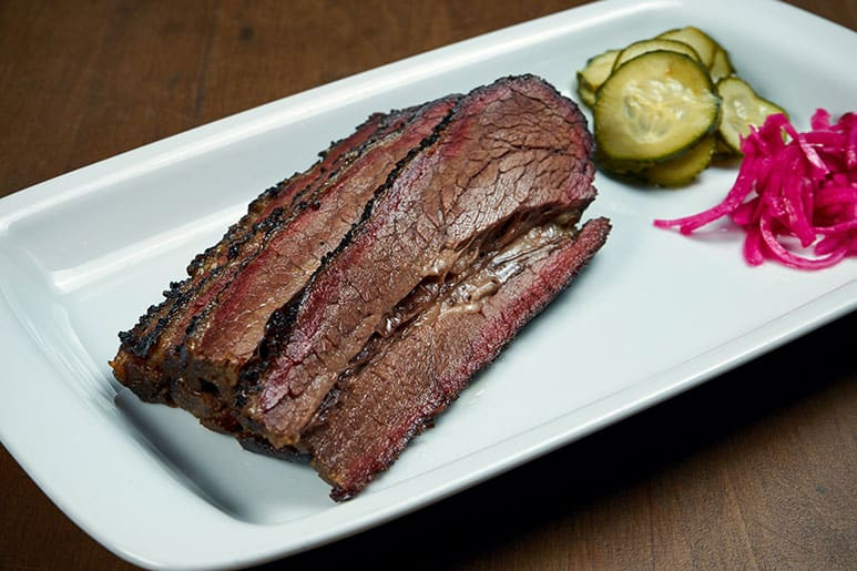 Image of a smoked brisket with horse radish and cucumbers laid out in a plate