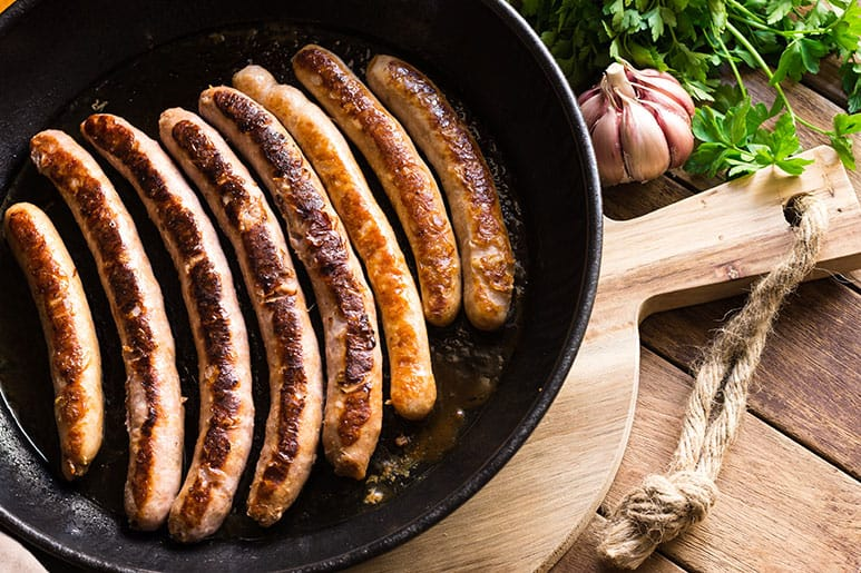Image of cooked sausages in a nonstick frying. To the side is a clove of garlic and some mint