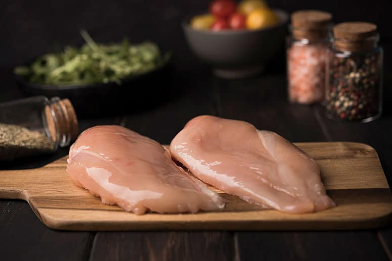 Image of two boneless skinless breasts on a wooden plank