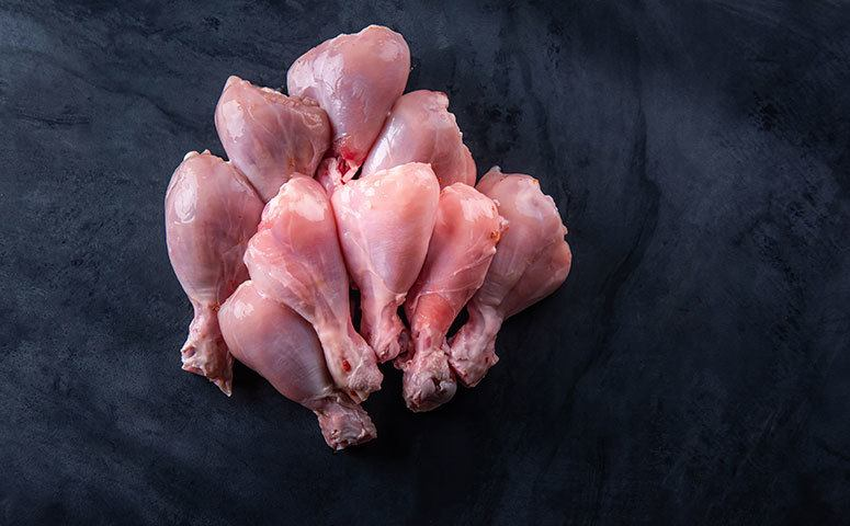 A bunch of skinless chicken legs on table top in the kitchen.