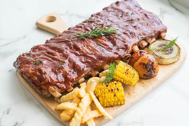 Image of a plate of ribs with a side of fries and corn