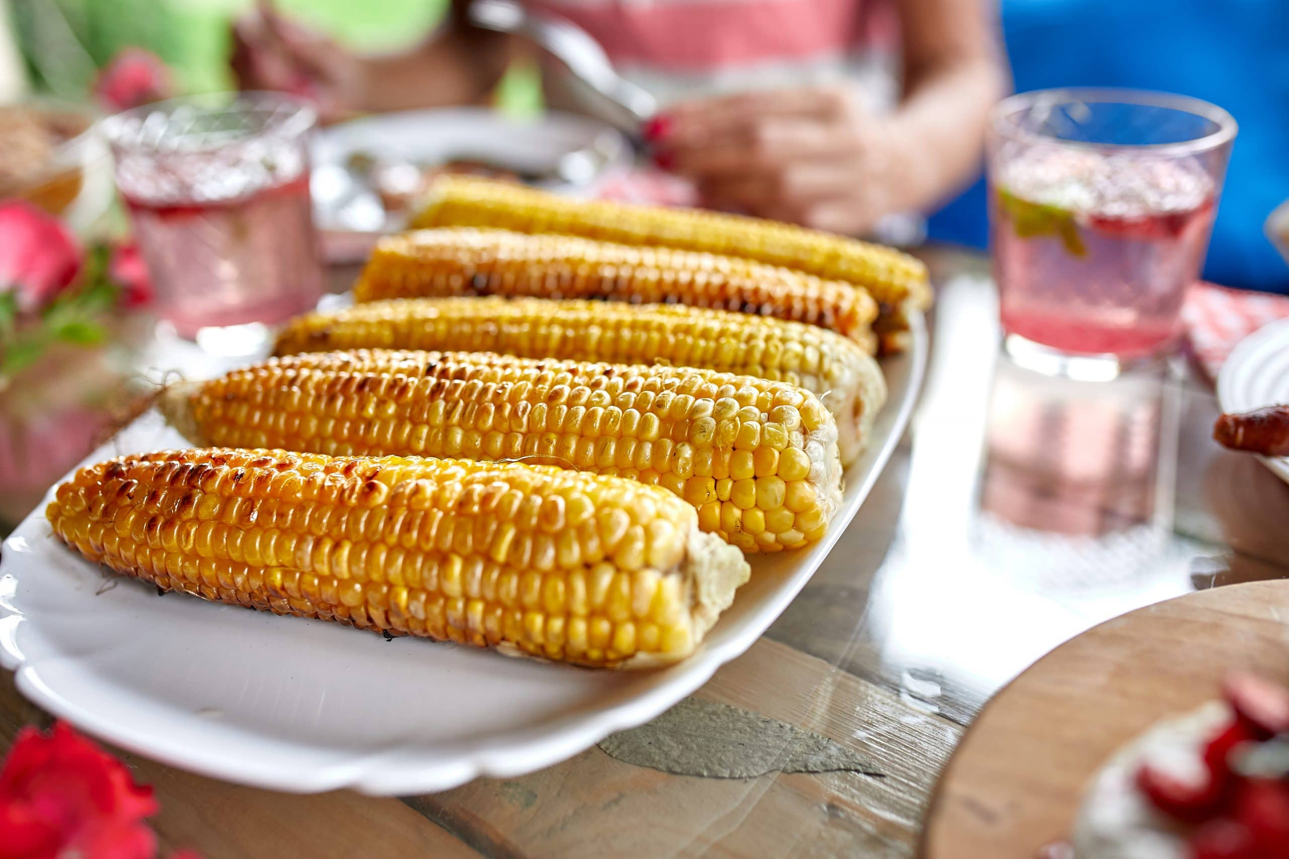 Grilled corn cobs on plate on the dinner table, appetizers variety serving on party outdoor table at home.
