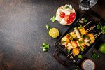 Image of Paneer Tikka on a black plate surrounded by lemon and cherry tomatos